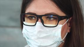 Face of female scientist or doctor in white protective mask. Close up view stock footage
