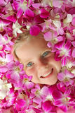 Face Floating in Flowers. Face of pretty child surrounded by pink orchids Stock Photo