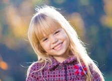 Face, fun, close up. Beautiful little blonde hair girl, has fun smile face, happy brown eyes, white teeth. Child portrait. Creative concept. Autumn time. Close royalty free stock image