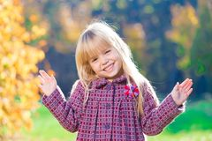 Face, fun, close up. Beautiful little blonde hair girl, has fun smile face, happy brown eyes, white teeth. Child portrait. Creative concept. Autumn time. Close stock image