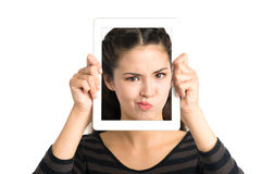 Face in gadget. Portrait of a girl holding a modern gadget with a face in it isolated on white stock photography