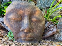 Stone face in the garden. Face in the garden, a portrait in stone Stock Photography