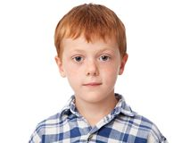 Face of a ginger boy. Close up face of a serious ginger boy isolated on white background royalty free stock photography