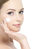 Face of girl applying cream Stock Photos