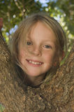 Face of girl climbing tree Stock Photos