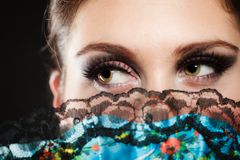 Face of girl flamenco dancer hidden behind fan. Portrait of attractive brunette woman. Closeup of face of spanish girl flamenco dancer hidden behind fan Royalty Free Stock Images