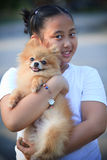 Face of girl holding pomeranian dog in home garden Stock Images