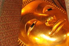 Face of Golden reclining buddha statue,Thailand Stock Photo