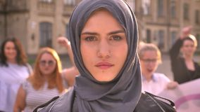 Face of gorgeous caucasian girl in hijab looks precisely with feminist show behind stock footage