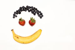 The Face. Hair of blueberries, eyes of strawberries and mouth of banana Royalty Free Stock Photo