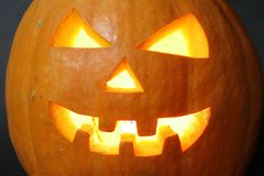 Face of halloween pumpkin. On black background with candle inside Royalty Free Stock Images