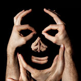 Face hands concept. Realty manipulation illusion. Black background Stock Photography