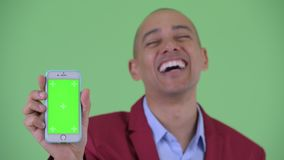 Face of happy bald multi ethnic businessman showing phone. Studio shot of handsome bald multi ethnic businessman against chroma key with green background stock video footage