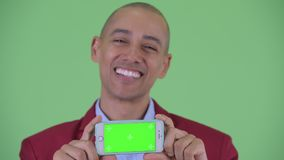 Face of happy bald multi ethnic businessman thinking while showing phone. Studio shot of handsome bald multi ethnic businessman against chroma key with green stock footage