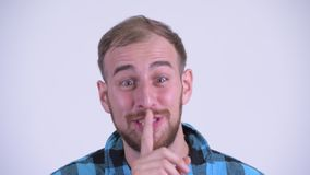 Face of happy bearded hipster man with finger on lips. Studio shot of bearded hipster man against white background stock footage