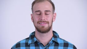 Face of happy bearded hipster man relaxing with eyes closed. Studio shot of bearded hipster man against white background stock footage