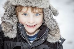 Face of happy boy in winter hat. A face of smiling toddler boy with blue eyes in Eskimo furry winter hat and coat outside in the snow stock images