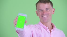 Face of happy businessman showing phone. Studio shot of businessman wearing pink shirt against chroma key with green background stock footage