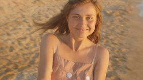 Face of a happy girl spinning round at sunrise, woman holding hands of her beloved man, honeymoon at seashore, romantic vacation. Slow motion stock video footage
