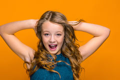 The face of happy teen girl. With long hair on orange studio background Stock Photography