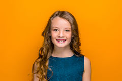 The face of happy teen girl. With long hair on orange studio background Stock Photo