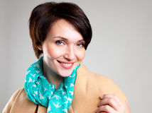 Face of Happy woman in autumn coat with green scarf. Face of happy woman in beige autumn coat with green scarf at studio on the grey background stock photography