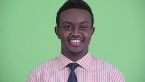 Face of happy young African businessman with Afro hair smiling. Studio shot of young African businessman with Afro hair against chroma key with green background stock video