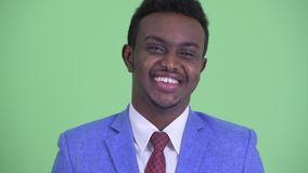 Face of happy young African businessman nodding head yes. Studio shot of young African businessman with Afro hair wearing suit against chroma key with green stock video