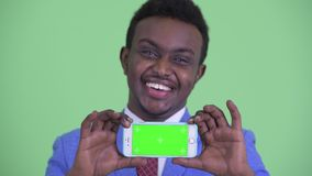 Face of happy young African businessman showing phone. Studio shot of young African businessman with Afro hair wearing suit against chroma key with green stock footage
