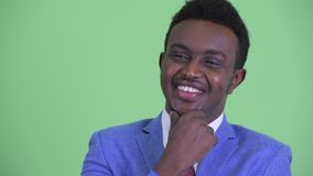 Face of happy young African businessman thinking. Studio shot of young African businessman with Afro hair wearing suit against chroma key with green background stock footage