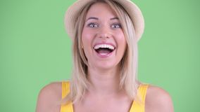 Face of happy young blonde tourist woman looking surprised