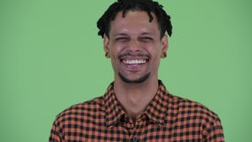Face of happy young handsome African man smiling and laughing. Studio shot of young handsome African man with dreadlocks against chroma key with green background stock video footage