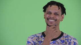 Face of happy young handsome African man thinking and looking up. Studio shot of young handsome African man with dreadlocks against chroma key with green stock video footage
