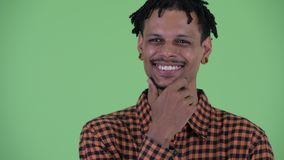 Face of happy young handsome African man thinking and looking up. Studio shot of young handsome African man with dreadlocks against chroma key with green stock footage