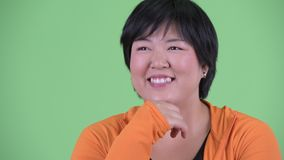 Face of happy young overweight Asian woman thinking and looking up ready for gym. Studio shot of young beautiful overweight Asian woman ready for gym against stock video footage