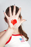 Face Heart. The girl closed the person at hand with the heart symbol on a gray background royalty free stock photos