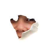 Face In A Hole. A childs face looking through a hole, isolated against a white background royalty free stock images