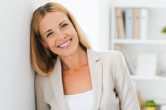 Face of job satisfaction. Beautiful mature businesswoman looking at camera and smiling while leaning at the wall Royalty Free Stock Photography