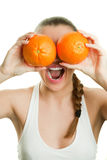 Face of joyful girl holding oranges by her eyes an. D laughing studio shot royalty free stock image