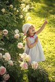 Face kid for magazine cover. Girl kids face portrait in your advertisnent. Innocence, purity and youth concept. Girl in hat pointing finger in summer garden Stock Image