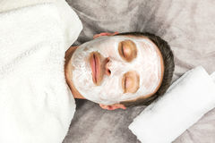 Face of laying man with cream mask with white towels Stock Photo