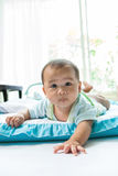 Face of little baby lying on children bed in home living room Royalty Free Stock Image