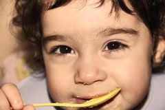 Face of little child close up, eating with spoon Royalty Free Stock Photos