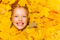 Face of little smiling blond girl in maple leaves Royalty Free Stock Photo