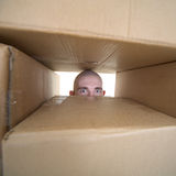 Face looking trough window in pile cardboards. Male face looking trough window in pile cardboards stock photography