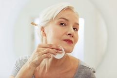 Pleasant good looking woman cleaning her face. Face lotion. Pleasant good looking woman using a cotton pad while cleaning her face royalty free stock image