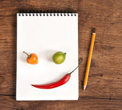Face made of vegetables. Studio photography of open blank ring bound notebook and pencil on old wooden table Stock Images