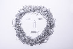 Face make from paper clips on white royalty free stock images