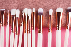 Face makeup brushes on pink and brown background. Royalty Free Stock Photo