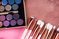 Face makeup brushes on pink and brown background. Royalty Free Stock Image